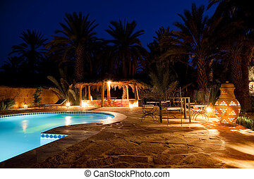 Pool and garden of a maroccan kasbah hotel at night, Maroc, Africa.