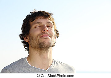 Attractive man breathing outdoor with the sky in the background