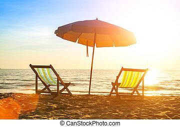 Beach loungers on deserted coast sea at sunrise.