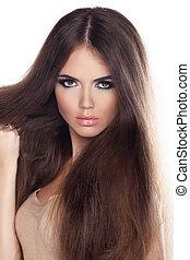 Beautiful woman with long brown hair. Closeup portrait of a fashion model posing at studio.
