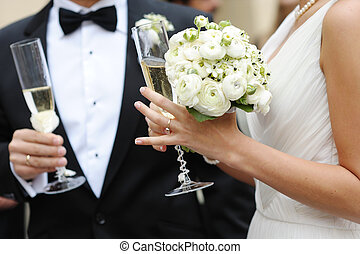Bride and groom are holding champagne glasses