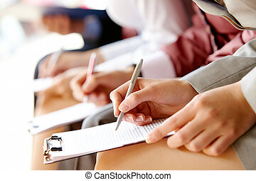 Businesspeople hands over papers making notes at seminar