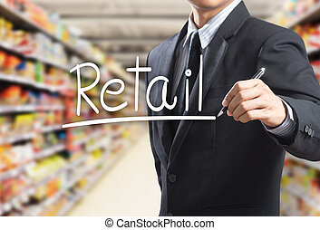 Business man writing word retail in the supermarket