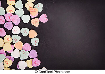 Candy conversation hearts on a chalkboard