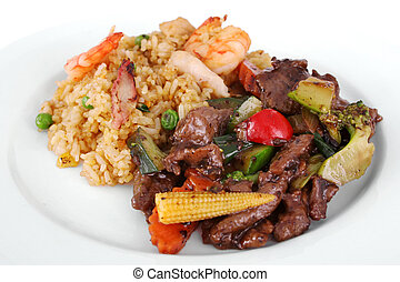 A meal of beef and black bean sauce served with the chefs special fried rice on a white plate.