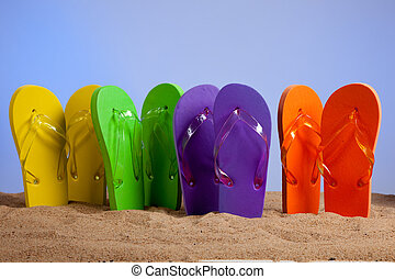 Four pairs of colorful flip-flop sandles on a beach background, studio shot