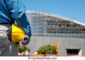 A construction worker or foreman at a construction site with blue prints and a hard hat