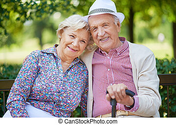 Happy seniors sitting in the park and looking at camera