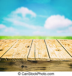 Close-up of an empty wooden table outdoors, in the countryside, with a blurred green field and a cloudy sky in the background