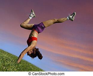 Girl exercising outdoors against sunset
