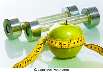 Close-up of green apple tied with measuring tape on the background of dumbbells