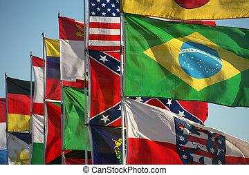 Waving international flags in blue sky