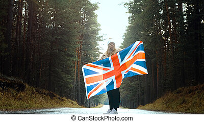 Girl holds the flag of United Kingdom in hands on the road