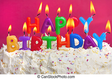 colourful lit candles spellign out happy birthday on a cake