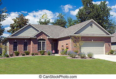 Beautiful brick ranch home against a blue cloudy sky.