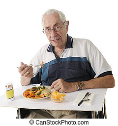 An elderly man eating a hospital meal in his wheelchair. On a white background.