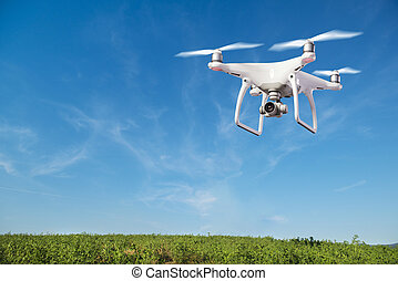 Close up of hovering drone against clear blue sky taking pictures of green hills