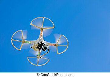 Hovering white drone in a vivid blue sky.