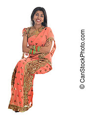 Full body traditional Indian woman in sari sitting on a transparent chair isolated over white background.