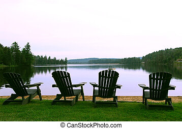 Four wooden adirondack chairs on a shore of a beautiful lake at dusk