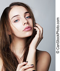 Beautiful young female face with a wellness complexion - isolated on grey