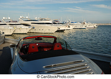 Luxury sports car and yachts in the harbor of Marbella, Spain