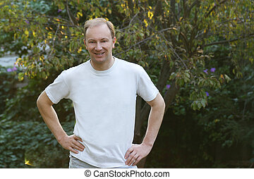 Man in a white Tshirt standing in a natural background.