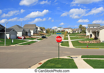 A stop sign at the intersection of a modern neighborhood