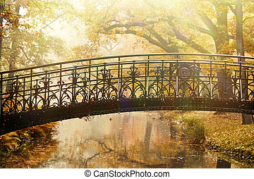 Old bridge in autumn misty park