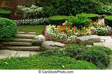 A quiet garden with flowers, shrubs and uneven stone stairs.
