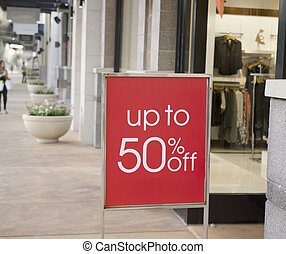 Sale sign outside retail store in shopping mall
