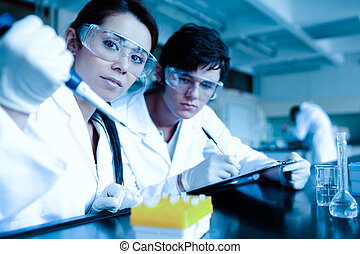 Science student dropping liquid in test tubes while her partner is taking notes in a laboratory