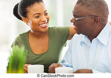 smiling elderly african american man enjoying coffee with his granddaughteer at home