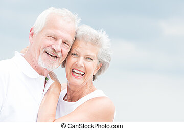 Happy and smiling couple in front of cloudy sky