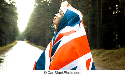 The girl holds the flag of United Kingdom in hands. Portrait shoot