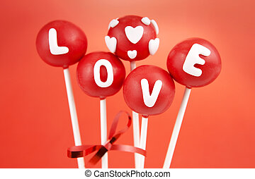 Red cake pops garnished with letters and hearts