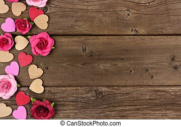 Valentines Day side border of hearts and roses against rustic wood