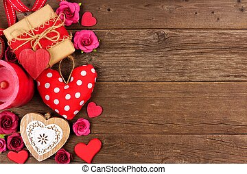 Valentines Day side border of hearts, gifts, flowers and decor on rustic wood