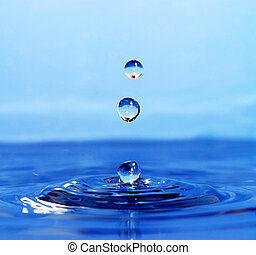 The round transparent drop of water falls downward