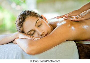 An attractive caucasian woman lying down on a massage bed at a spa