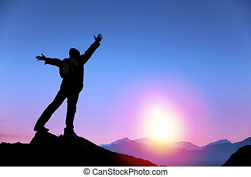 young man standing on the top of mountain and watching the sunrise